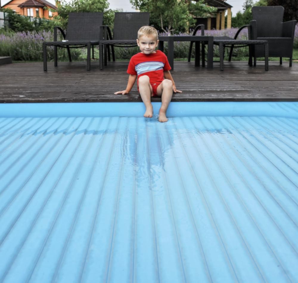 enfant sur couverture piscine